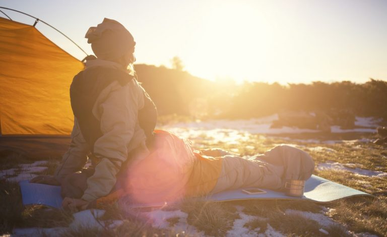 Female hiker sitting with a heated blanket in a snowy landscape next to her tent an enjoying the sunset