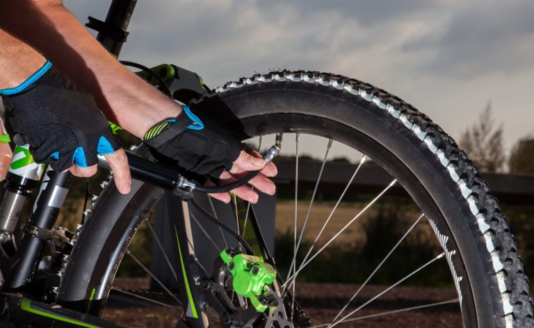 Mountain biker pumping air into his mountain bike