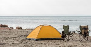 Orange tent set up on a windy beach with a couple of camping chairs by the side