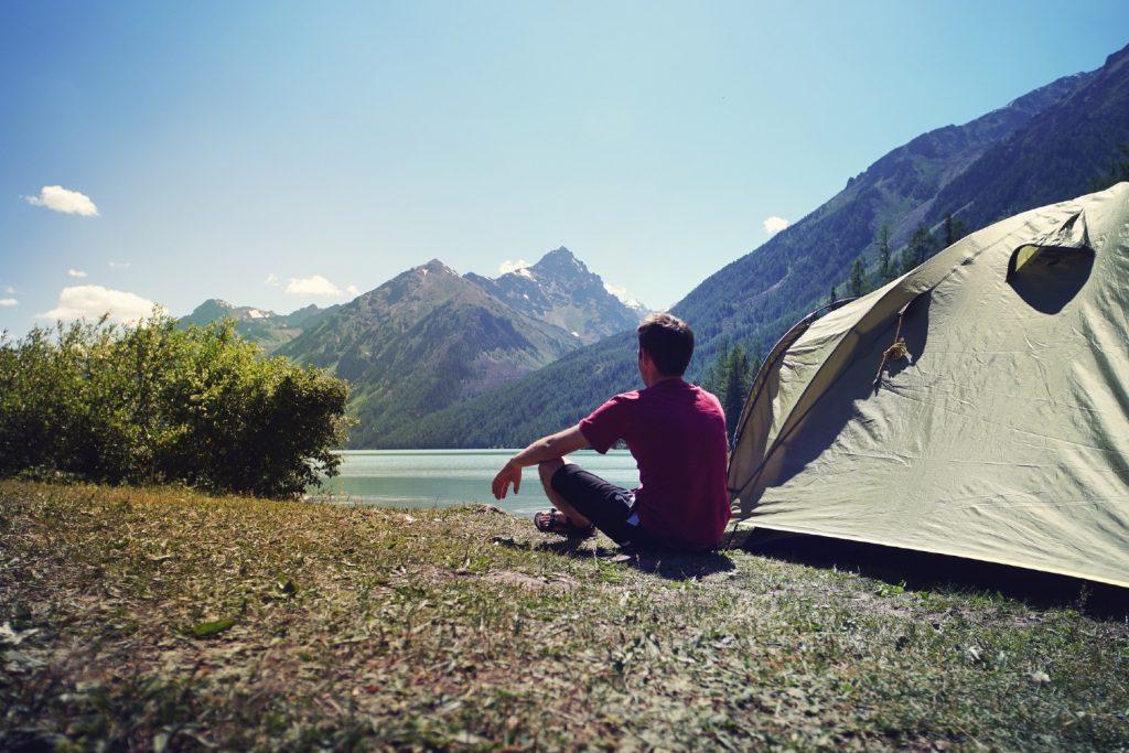 Man sitting next to tent enjoying the view