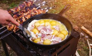 Cooking breakfast in cast iron skillet over a camp fire