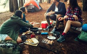 People enjoying their food at a camp fire
