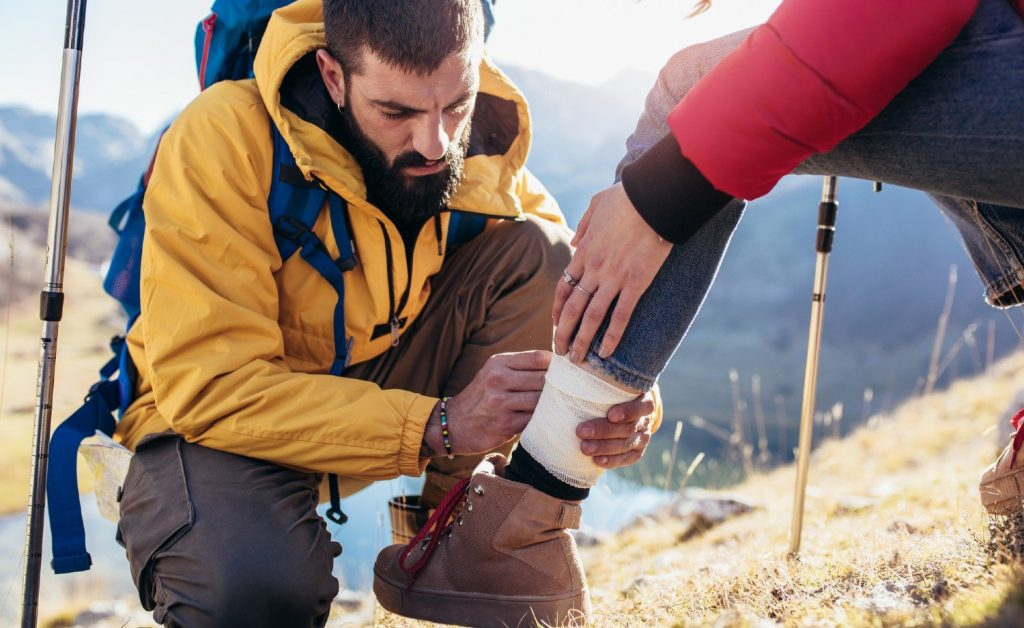 Woman with sprained ankle gets help from a friend using a first aid kit on a hike