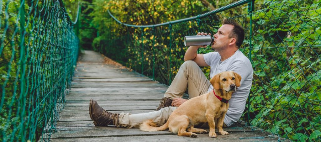 Man taking a break during a hike with his dog