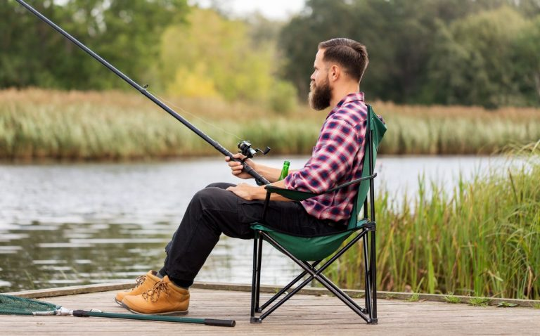 Man sitting in his folding chair while fishing at a lake