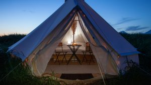 Glamorous yurt style tent with sunset in the background and lights inside