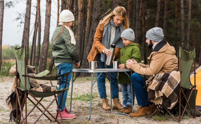 Family preparing a meal at a folding table in a forest camp ground