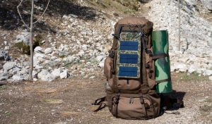 Backpacker utilizing his solar charger while hiking