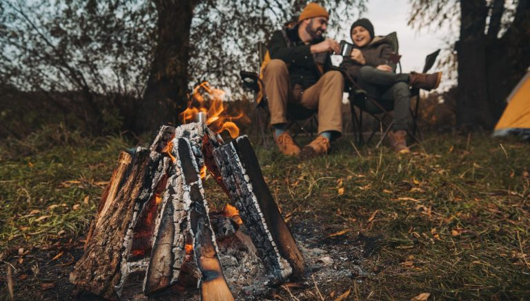Friends sitting next to a campfire near a camp ground