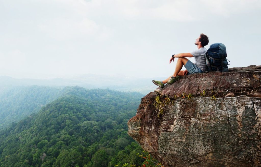 Male hiker taking a rest at the edge of a cliff while taking in the views of nature